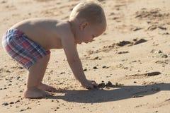 Śmieszny berbeć bawić się z piaskiem na plaży Śliczna chłopiec zabawę na wakacjach zdjęcia royalty free