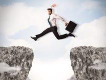 Śmieszny biznesowy mężczyzna skacze nad skałami z przerwą Zdjęcie Royalty Free