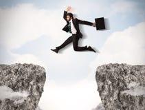 Śmieszny biznesowy mężczyzna skacze nad skałami z przerwą Obrazy Royalty Free
