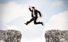 Śmieszny biznesowy mężczyzna skacze nad skałami z przerwą Zdjęcie Stock