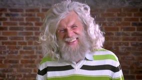 Śmieszny caucasian dziad jest roześmiany z zębami, krzaka białym włosy i długą brodą, nowożytna trwanie samiec, ściana z cegieł