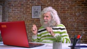 Śmieszny caucasian dziad z długą białą brodą i włosy jest siedzący szczęśliwie i tanczący w krześle podczas gdy patrzejący