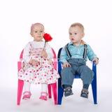 Śmieszny chłopiec i dziewczyny obsiadanie na krzesłach na bielu fotografia royalty free