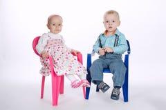 Śmieszny chłopiec i dziewczyny obsiadanie na krzesłach z powrotem popierać Obrazy Royalty Free
