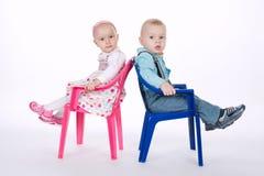 Śmieszny chłopiec i dziewczyny obsiadanie na krzesłach z powrotem popierać fotografia royalty free