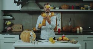 Śmieszny czas w kuchni przygotowywa dekorację dla Halloween przyjęcia mężczyzna, on zaczyna bawić się z niektóre pomarańczami zdjęcie wideo
