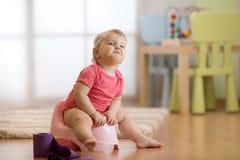 Śmieszny dziecka obsiadanie na sala garnku z papier toaletowy rolką fotografia royalty free