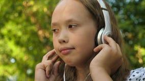 Śmieszny dziecko słucha muzyka Szcz??liwa dziewczyna s?ucha muzyka i taniec w lato parku w he?mofonach z bliska zbiory wideo