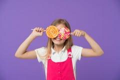Śmieszny dziecko z lizakami na fiołkowym tle Dziewczyna ono uśmiecha się z cukierków oczami Małe dziecko uśmiech z cukierkami na  obraz royalty free