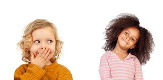 Śmieszny dziecko zakrywa jego usta i dziewczyny z afro włosiany patrzeć Zdjęcie Royalty Free