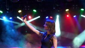 Śmieszny dziewczyna taniec w klubie nocnym i robi selfie zbiory