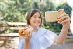 Śmieszny dziewczyny mienia hotdog w ręce i brać selfie w parku Zdjęcie Royalty Free