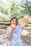 Śmieszny dziewczyny mienia hotdog w ręce i brać selfie w parku Fotografia Royalty Free