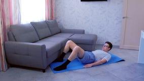 Śmieszny głupka mężczyzna robi pośladka mostu ćwiczeniu na macie umacniać mięśnie nogi w domu Sporta humor zbiory