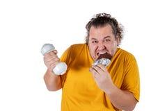 Śmieszny gruby mężczyzna je niezdrowego jedzenie i próbuje brać ćwiczenie odizolowywającego na białym tle obraz royalty free