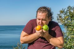 Śmieszny gruby mężczyzna na oceanu łasowania owoc Wakacje, ciężar strata i zdrowy łasowanie, fotografia royalty free