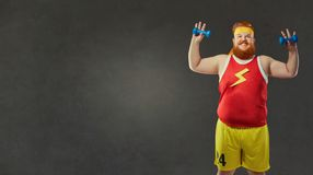 Śmieszny gruby mężczyzna ono uśmiecha się w sportach odziewa z małymi dumbbells obrazy stock