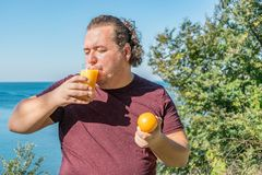 Śmieszny gruby mężczyzna pije sok i je owoc na oceanie Wakacje, ciężar strata i zdrowy łasowanie, obrazy royalty free