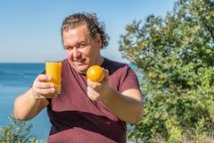 Śmieszny gruby mężczyzna pije sok i je owoc na oceanie Wakacje, ciężar strata i zdrowy łasowanie, fotografia stock