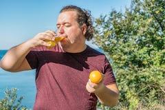 Śmieszny gruby mężczyzna pije sok i je owoc na oceanie Wakacje, ciężar strata i zdrowy łasowanie, zdjęcia royalty free