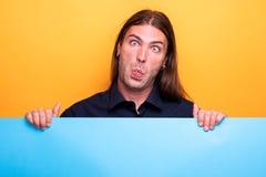 Śmieszny grymas na mężczyzna twarzy podczas gdy displayng błękitny karton obrazy royalty free