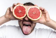 Śmieszny i dobry obrazek stawia dwa przyrodniego kawałka grapefruitowy na jego oczach dorosły mężczyzna Także pokazuje jego jęzor zdjęcia royalty free
