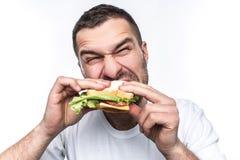 Śmieszny i głodny facet je niektóre fast food Jest głodny jak wilk Mężczyzna gryźć kanapkę bardzo mocno Odizolowywający dalej fotografia royalty free