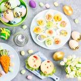 Śmieszny kolorowy Wielkanocny jedzenie dla dzieciaków z dekoracjami na stole Wielkanocny obiadowy pojęcie obraz royalty free