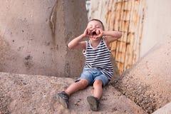 Śmieszny krzyczący chłopiec obsiadanie na falochronie na molu Obrazy Stock
