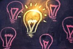 Śmieszny lightbulb na blackboard, pojęcie jedyność zdjęcia stock