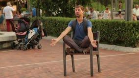 Śmieszny mężczyzna medytuje w lotosowej pozyci na krześle przy parkiem, zabawny społeczeństwo zbiory