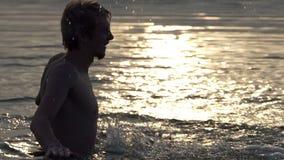 Śmieszny mężczyzna podnosi strumienie woda w jeziorze przy zmierzchem w mo zbiory