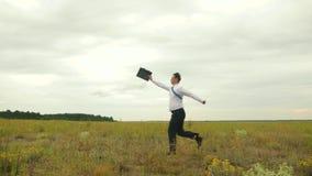 ?mieszny m??czyzna z teczk? galopuje przez pole Szcz??liwy biznesmen raduje si? i skacze na polu z teczk? zbiory wideo