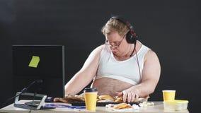 Śmieszny młody człowiek w słuchawki z komputer osobisty komputerową bawić się grze w domu zbiory