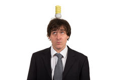 Śmieszny młody człowiek z żarówką nad jego głową, odosobnioną na białym tle zdjęcie royalty free