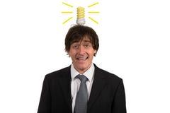 Śmieszny młody człowiek z żarówką nad jego głową, odosobnioną na białym tle Zdjęcia Stock