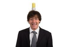 Śmieszny młody człowiek z żarówką nad jego głową, odosobnioną na białym tle Fotografia Royalty Free