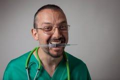 Śmieszny młody lekarz trzyma strzykawkę z jego zębami fotografia stock