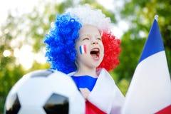 Śmieszny małej dziewczynki zachęcanie, doping i jej krajowa drużyna futbolowa obraz royalty free