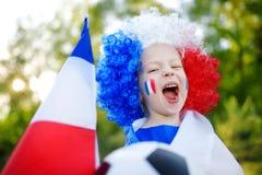 Śmieszny małej dziewczynki zachęcanie, doping i jej krajowa drużyna futbolowa fotografia stock