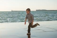 Śmieszny mały caucasian dzieciaka bieg wzdłuż dennego brzeg w portowy grodzki plenerowym zdjęcia stock