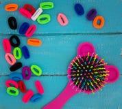 Śmieszny Różowy dziecka hairbrush i stubarwni gumowi zespoły dla włosy zdjęcie royalty free