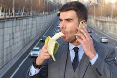 Śmieszny smiley biznesmen trzyma banana podczas gdy dzwoniący telefonem Zdjęcie Royalty Free