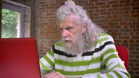 Śmieszny starszy caucasian szarość mężczyzna pisać na maszynie w jego obsiadaniu w nowożytnym ceglanym biurze z jego twarzą skupi