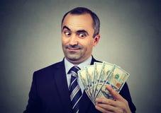 Śmieszny szczwany biznesowy mężczyzna trzyma patrzeć pieniądze dolara banknoty Fotografia Stock
