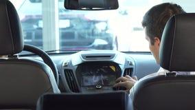 Śmieszny tata z jego córką siedzi w miejsce na przedzie i patrzeje małego ekran samochód zbiory wideo
