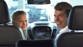Śmieszny tata z jego córką siedzi w miejsce na przedzie i patrzeje małego ekran samochód obrazy stock