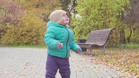 Śmieszny uśmiechający się 1 roczniak chłopiec odprowadzenie w jesień parku przy zmierzchem z chlebem w ręce szczęśliwy dzieciństw zbiory wideo