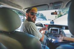 Śmieszny uśmiechnięty bearding mężczyzna z szkłem winograd w samochodzie Zdjęcia Royalty Free