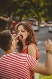 śmieszny wąs Piękna młoda kochająca para robi sfałszowanemu wąsowi od włosy podczas gdy siedzący outdoors przy zieloną miasto uli Fotografia Stock